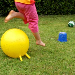 Kind durchläuft einen Parcour aus Hüpfball, Eimer und Fussball