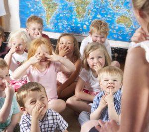 Kindergartenkinder tippen sich fröhlich an die Nase und singen