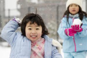 kleine Mädchen machen eine Schneeballschlacht