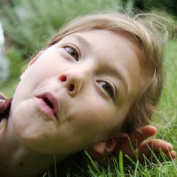 kleines Mädchen liegt auf dem Rasen und lauscht