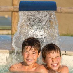 Zwei Jungen unter dem Wasserstrahl im Swimmingpool
