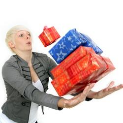 Frau fällt ein Stapel Geschenke aus der Hand