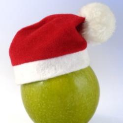 grüner Apfel mit einer Weihnachtsmütze