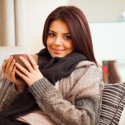 Junge Frau mit einer Tasse auf dem Sofa