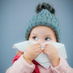 Kleines Mädchen mit Bommelmütze benutzt ein Taschentuch