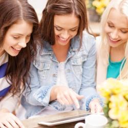 Drei Erzieherinnen schauen sich Fotos aus dem letzten Jahr an