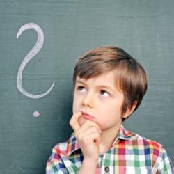 kleiner Junge vor einer Tafel mit Fragezeichen
