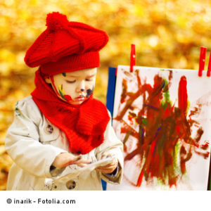 Child drawing on easel in Autumn Park
