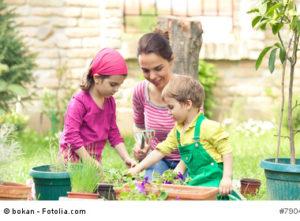 Erzieherin mit Kindern bei der Gartenpflege