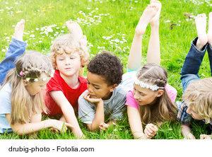 Kita-Kinder liegen auf einer Wiese