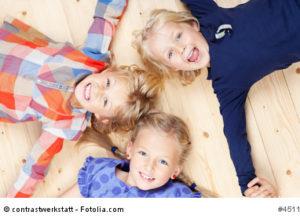 Kita-Kinder liegen auf dem Boden