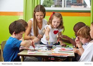 Kita-Kinder mit ihrer Erzieherin beim Malen
