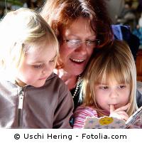 Erzieherin mit Kindern auf dem Schoß