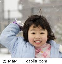 Kleines Mädchen wirft einen Schneeball